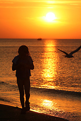 Silhouette of little girl walking on beach at sunset