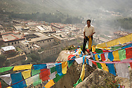 A man hangs Tibetan prayer flags during a religious festival at Drepung Monastery in Lhasa, Tibet.