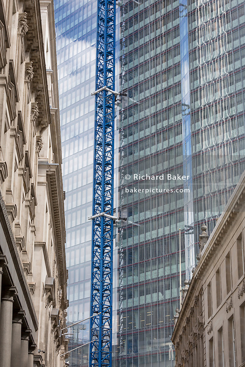 Old architecture and the new development high-rise development at 22 Bishopsgate in the City of London - the capital's financial district, on 21st August 2018, in London, England. 22 Bishopsgate is a commercial skyscraper under construction in London, United Kingdom. It will occupy a prominent site on Bishopsgate, in the City of London financial district, and is set to stand 278 m tall with 62 storeys. The project replaces an earlier plan for a 288 m tower named The Pinnacle, on which construction was started in 2008 but suspended in 2012 following the Great Recession,