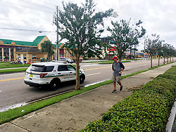 "An Orange County Sheriff's deputy stops a tourist on International Drive and tells him to go back to his hotel. On loudspeaker, one said, ""You can be arrested. There are downed power lines. It's still dangerous."" Photo by Orlando Sentinel/TNS/ABACAPRESS.COM"
