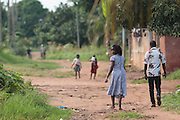 A woman and a man walk down a dirt road in Katiola, Cote d'Ivoire on Saturday July 13, 2013.