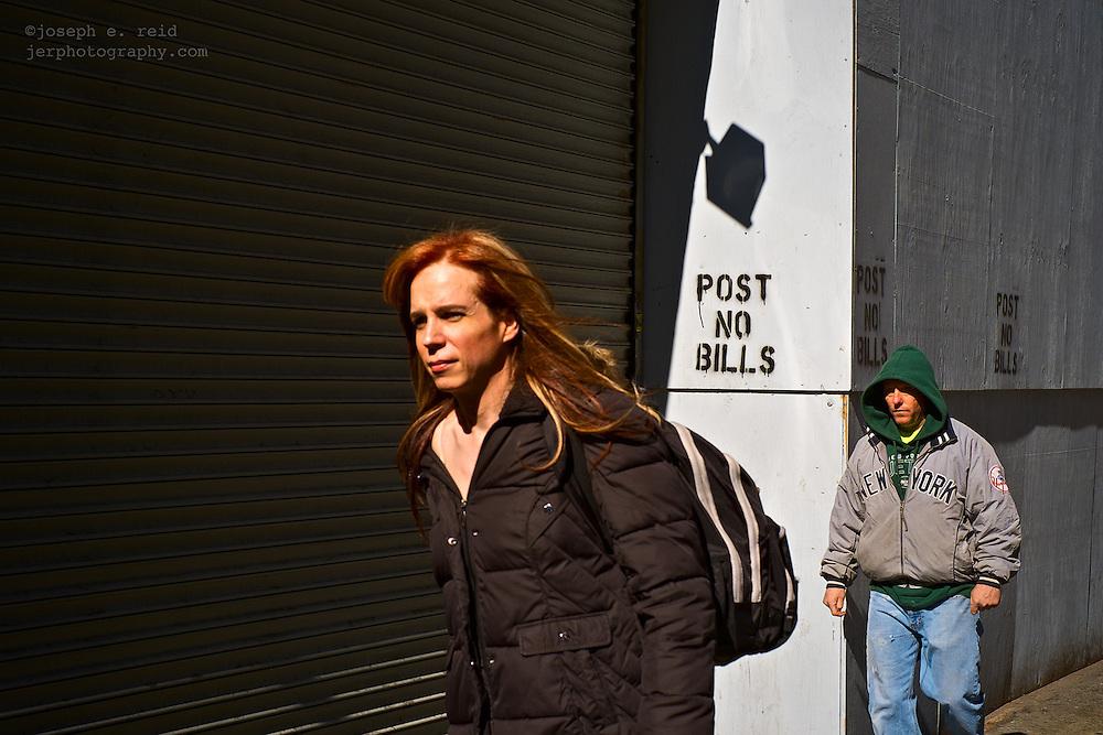 Man in Yankees jacket walking behind woman with red hair