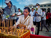 01 JANUARY 2019 - BANGKOK, THAILAND:   A woman lights incense at the New Year's merit making ceremony on the plaza in front of City Hall in Bangkok. City Hall traditionally hosts one of the largest New Year merit making ceremonies in Thailand. This year about 160 monks participated in the event.    PHOTO BY JACK KURTZ