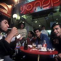 Israel, Jerusalem, Group of men sit at cafe table along Ben Yehuda Street on spring evening