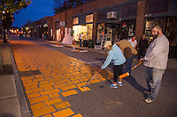 Michelle Albert, Tom Menard and Izzy Brake paint Canal Street orange on Wednesday evening transforming it into PumpCanaly for Pumpkin Fest on Saturday.  (Karen Bobotas/for the Laconia Daily Sun)