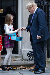 © Licensed to London News Pictures. 28/10/2019. London, UK. Prime Minister Boris Johnson (R) outside 10 Downing Street as he buys a poppy for the Royal British Legion Poppy Appeal. The EU has agreed to extend the Brexit deadline. Later today MPs will vote on whether to hold a general election in early December. Photo credit: Rob Pinney/LNP