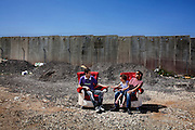 Two furniture makers take a break in the open air on a pair of plush armchairs, of their own creation, in Hizma in the West Bank. Israel's 26-foot high Separation Wall stretches behind them.