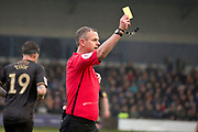 Referee C Sarginson shows yellow to Mansfield Town defender Malvind Benning (not in the picture)  during the EFL Sky Bet League 2 match between Macclesfield Town and Mansfield Town at Moss Rose, Macclesfield, United Kingdom on 16 November 2019.