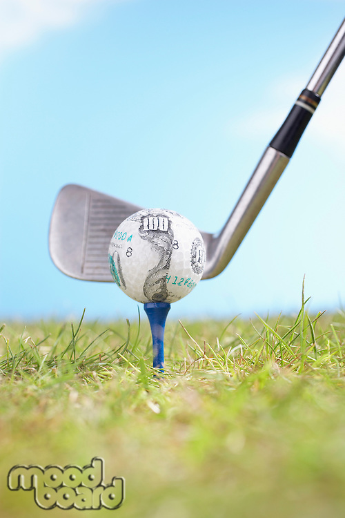 Teeing Off Golf Ball Covered in 100-Dollar Bill