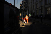 A Stop / Go banksman dressed in a high-vis suit stands on a public road for oncoming traffic
