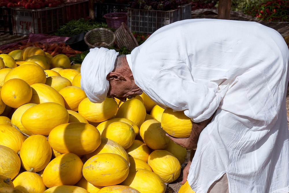 Man at a pile of canary melons at the market in Zagora, Morocco.