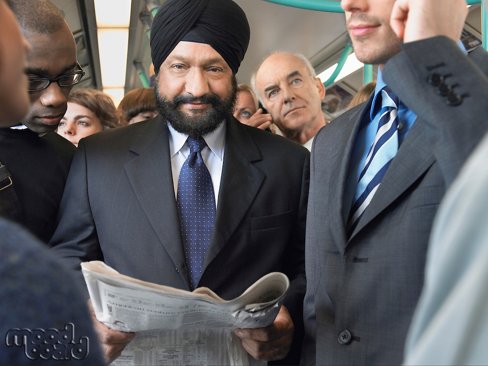 Commuter in turban Reading paper on Train