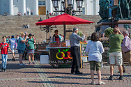 """Helsinki, Finland -- July 19, 2019. A vendor has a juice cart set up by the stairs at Tuomiokirkko, the """"Big White Church""""."""