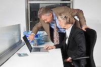 Side view of businesswoman and man looking at laptop screen at desk in office