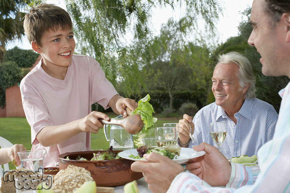 Boy (10-12) serving father at table in garden