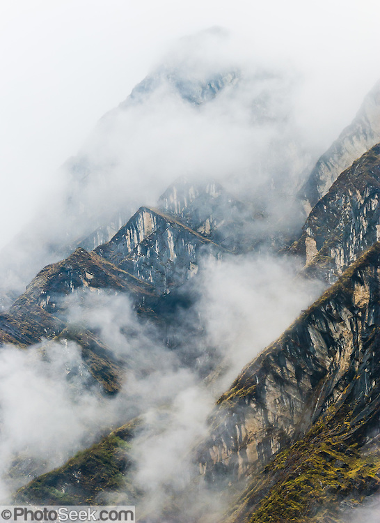 Peaks rise through the fog, above Deurali village (10,600 feet / 3231 meters elevation), in the deep valley of the Modi Khola river, in the Annapurna Mountain Range of Nepal.