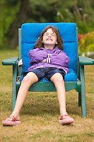 Young girl sitting in a chair making a funny face / smile.
