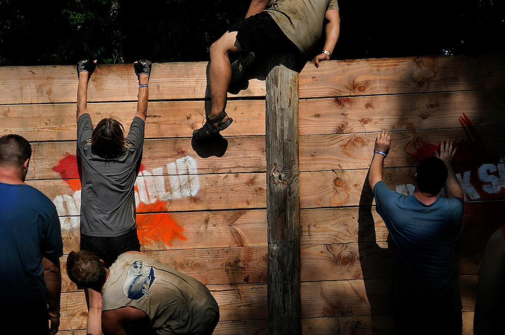 Participants make their way over a wall during the Rock Solid Mud Run held at Old Bridge Township Raceway Park in Englishtown on August 6. Rock Solid Mud Run is an all-terrain adventure that involves mastering obstacles along either a five or ten-mile course. Participants ran, swam, crawled, climbed, jumped while covering four motocross tracks, hundreds of acres of woods, three lakes, and two asphalt racetracks.