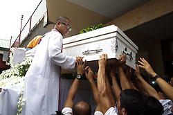 August 26, 2017 - Manila, Philippines - A priest helps sympathizers place the body of Kian Loyd Delos Santos on a hearse in Manila. Kian Loyd Delos Santos, a 17 year old high school student who was killed by policemen in an alleged shootout, has become a rallying point for activists and opponents of President Duterte to criticize the bloody war on drugs in the Philippines, which has claimed at least 7,000 lives and arresting more than 90,000, according to official data. (Credit Image: © Richard James M. Mendoza/Pacific Press via ZUMA Wire)