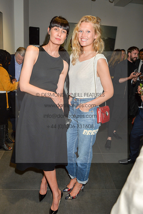 Left to right, models ERIN O'CONNOR and TONI GARRN, at a private view of woks by German artist Mike Dargas held at the Opera Gallery, 134 New Bond Street, London on 5th July 2016.