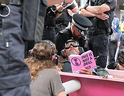 © Licensed to London News Pictures. 17/07/2019; Bristol, UK. Extinction Rebellion Summer Uprising 2019. A man sitting in a pink bath tub is locked onto the bath tub with his arm in a tube and police worked to remove him safely. Police remove protesters arresting some and putting them in police vans as they try to clear a major road junction occupied by an Extinction Rebellion protest which has caused major traffic disruption. Campaigners locked themselves onto a pink bath tub, and held 7 minute roadblocks on other parts of the junction complex. Extinction Rebellion are holding a five-day 'occupation' of Bristol, by occupying Bristol Bridge in the city centre and traffic has to be diverted and carrying out other events. As part of a country-wide rebellion called Summer Uprising, followers will be holding protests in five cities across the UK including Bristol on the theme of water and rising sea levels, which is the group's focus for the South West. The campaign wants the Government to change its recently-set target for zero carbon emissions from 2050 to 2025. Photo credit: Simon Chapman/LNP.