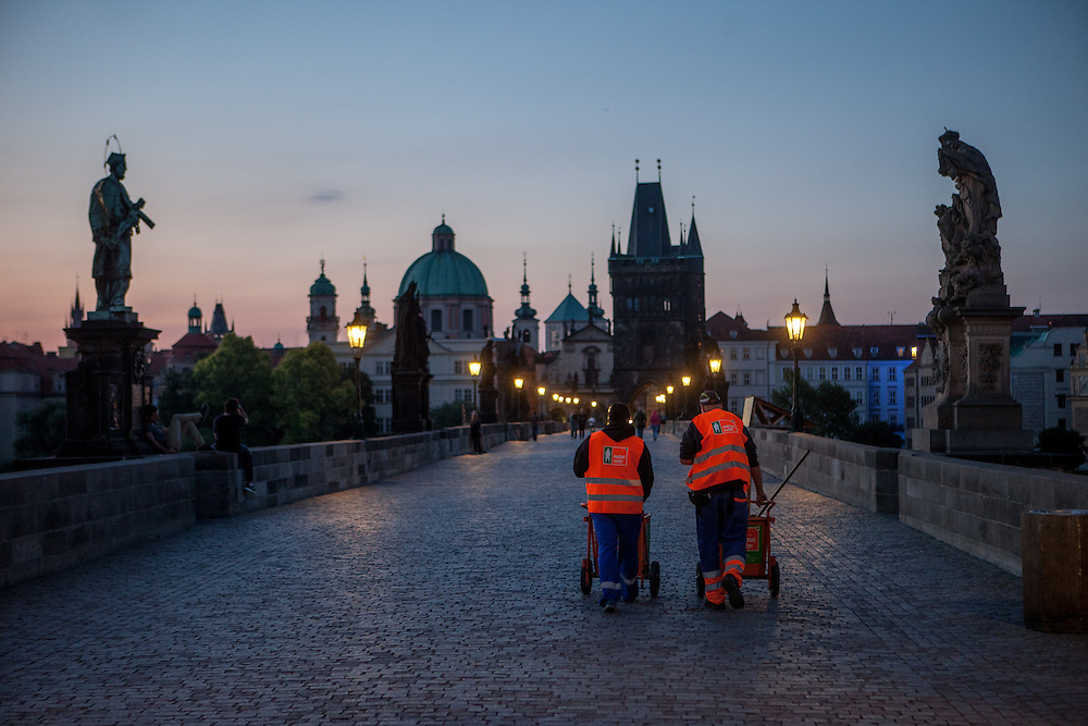 Charles Bridge and the view to Prague Old Town during the early morning change from night to day. Cleaning people from the city of Prague are going to work.