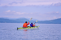 Dad and son share a double kayak in the Pacific Ocean near Mayne Island, BC