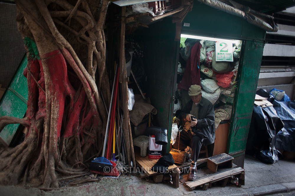 An old cobbler works on a boot in his small cobbler's workshop next to a tree in a hilly street in Mid-levels. 7 million people live on 1,104km square, making it Hong Kong the most vertical city in the world.