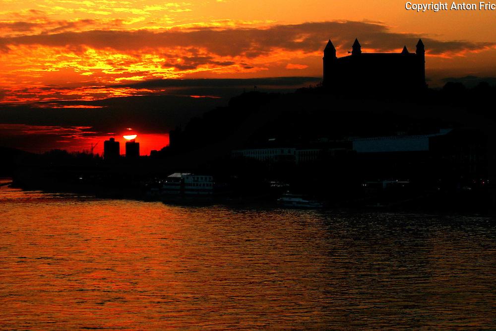 Sunset over Bratislava castle located in Bratislava - capital of Slovakia. Bratislava castle is towering over Danube river.