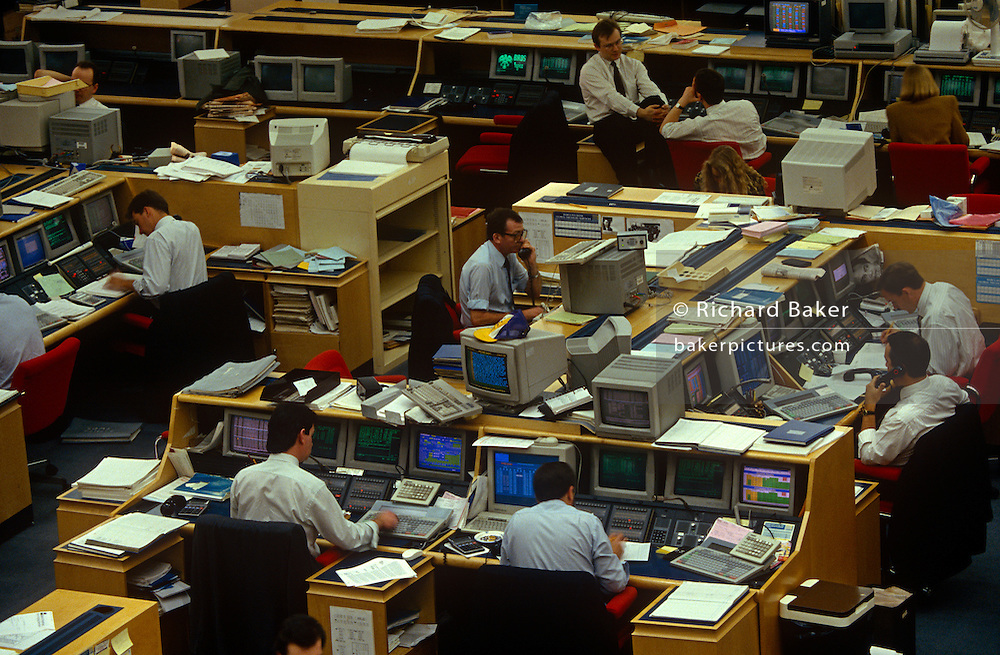 An interior of office desks and 90s computers in the trading floor of Barclays de Zoete Wedd in the City of London, the capital's financial centre. Screens glow with the most up to date trading figures and news items allowing traders to react instantly on the money markets.  .Employees talk on handsets or stare at their data near large keyboards and hard drives and deep monitors were state of the art technology in the early 1990s.