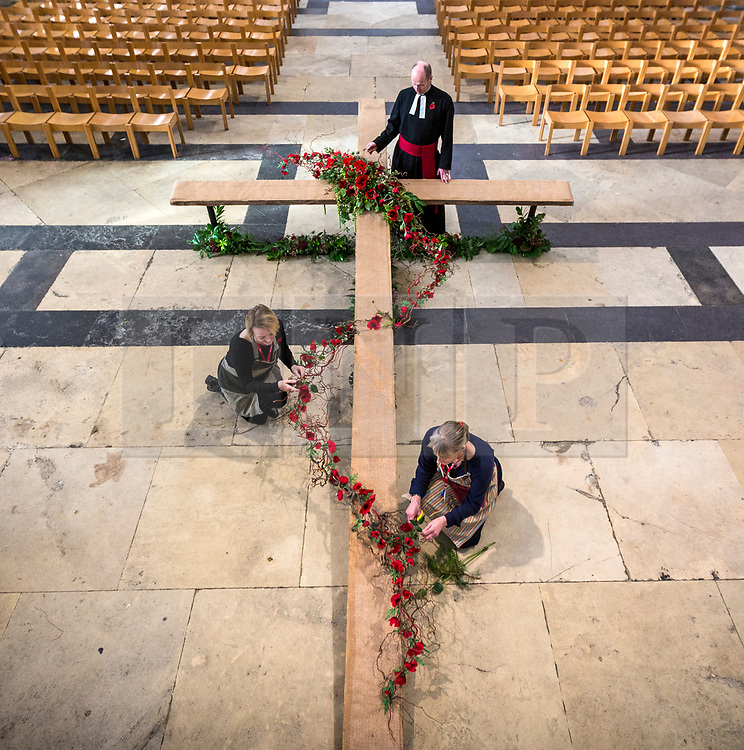 © Licensed to London News Pictures. 10/11/2018. York UK. Flower arrangers Julie Weston  & Mandy Baker along with Canon Michael Smith put the finishing touches to a 6 metre by 3.5 metre cross that is covered in silk poppies at York Minister.  The cross will will form the centre piece for the Armistice day service at the Minster tomorrow marking 100 years since the end of the First World War.  Photo credit: Andrew McCaren/LNP