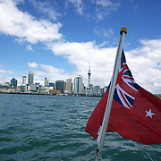 The New Zealand flag waves on the Historic Scow which sails for tourists form the NZ Maritime Museum, on the Auckland Harbour. Auckland, New Zealand, 4th November 2010. Photo Tim Clayton.