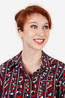 Happy young woman in shirt against gray background