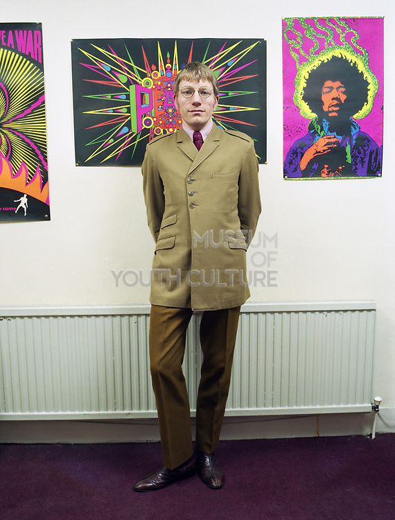 Young man standing in front of wall with neon posters including one of Jimi Hendrix.