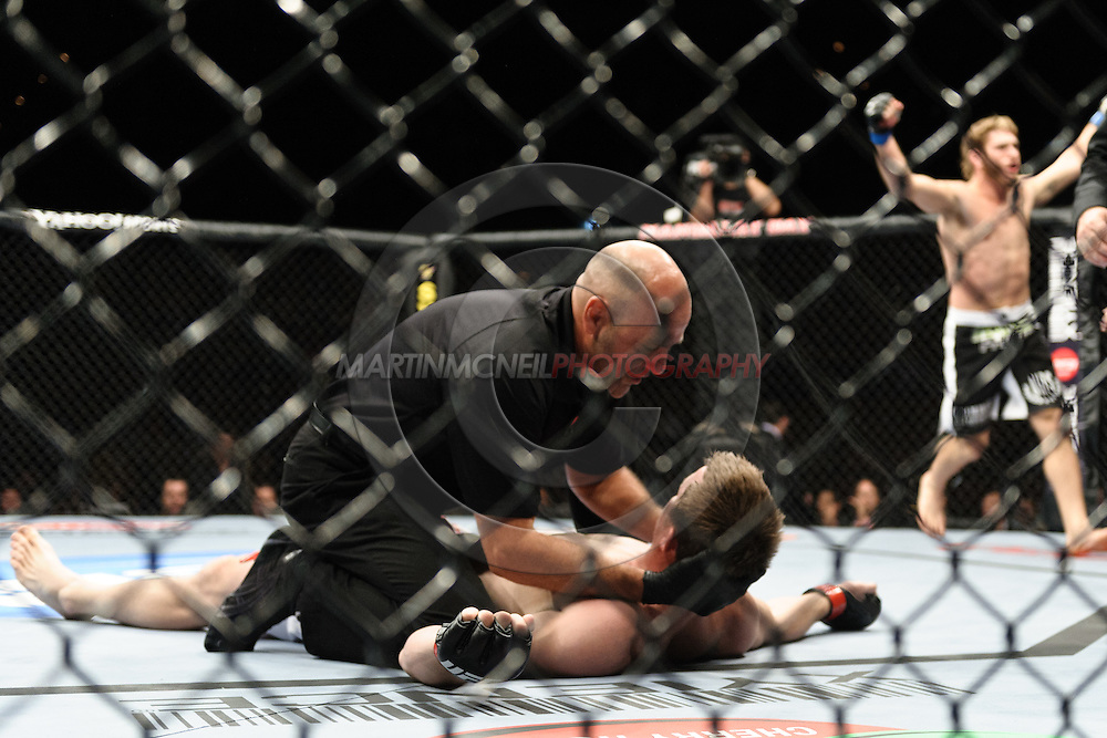 "LAS VEGAS, NEVADA. JULY 11, 2009: CB Referee Yves Lavigne checks on CB Dolloway as he lays on the canvas after losing his fight at ""UFC 100: Making History"" inside the Mandalay Bay Events Center in Las Vegas, Nevada."