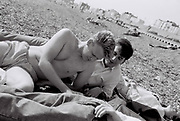 Men lying on Brighton Beach, UK, 1985