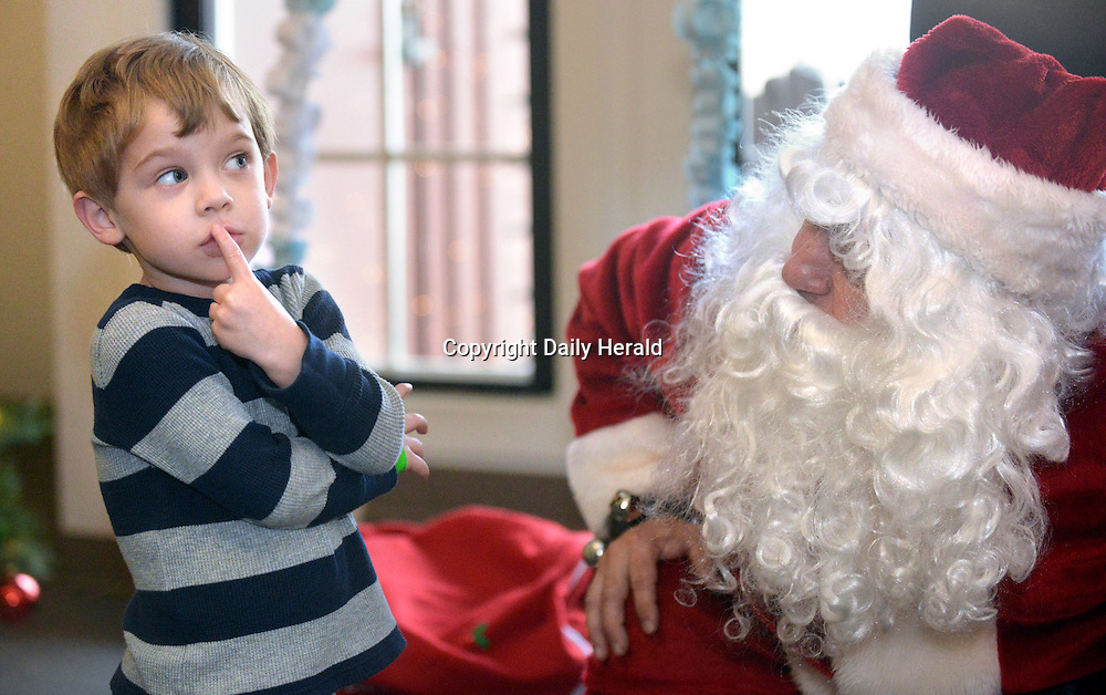 Christopher Tee, 3, of Geneva keeps a safe distance from Santa while he ponders what to ask for at Peck Farm Park in Geneva. This was the first time he had a one-on-one meeting with the jolly fellow and was a bit cautious at first. He decided on asking for a toy cash register.