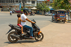 Sihanoukville, Cambodia -- March 17, 2016.  Little boy is riding on the back of a motorcycle, clinging to the driver. Motor bikes are a dominant mode of transportation in Sihanoukville. Editorial Use Only.