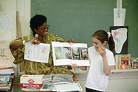 Asheville, North Carolina, USA --- With the assistance of her teacher, Mrs. Pea, Maggie Payne presents her class project to her fifth grade class. --- Image by © Owen Franken