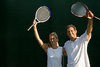 Tennis Partners Raising Rackets in Victory