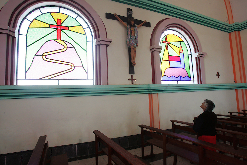 "A woman prays  at at church that Father Sebastian Obermaier built in El Alto, Bolivia. a town he has lived in for 27 years .  ""I don't feel Bolivian, I feel Aymara"" he says, referring to the Aymara indigenous population that makes up more than 80% of El Alto. Father Obermaier has been designing and building churches in El Alto for the past 10 years, with a goal of building one church for every 10,000 inhabitants of the city, which currently has nearly 700,000 people living in it.  Everyone that visits Bolivia can see his numerous churches from the window of their airplane as it lands in El Alto.  The churches are marked by a style unique to Father Obermaier, that mixes indigenous symbols with tall towers and bright colors, that leave every church looking different, as if they were straight out of a children's pop-up book."