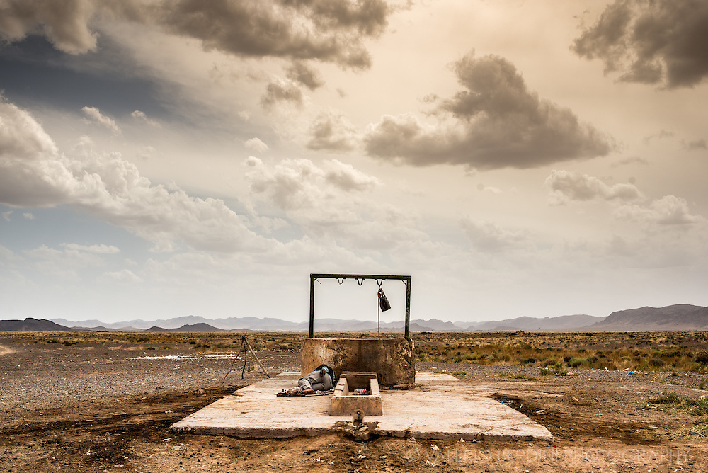 A man sleeps next to a well in the East Moroccan Sahara desert not far from the border with Algeria on 20 May 2015. Morocco, as well as Algeria, suffered a severe heatwave last summer with temperatures constantly above 40 degrees Celsius.  <br /> This photo was published on the Guardian, UK, on 24th August 2015. http://www.theguardian.com/environment/2015/aug/24/algeria-to-experience-more-heat-waves-due-to-climate-change-says-specialist