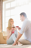 Happy couple looking at each other while having red wine at home