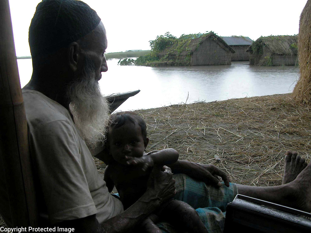 An umidentified old man is hearing flood reports from his transister (Radio) with his grand child, near his submerged houseby flood water at Bhashani village about 323 kilometers southwest of Gauhati, the capital city of Northeastern Indian state, Assam, Monday, June 28, 2004. ..Floodwaters of the Asia'a one of the largest river, Brahmaputra and its 35 tributaries have affected more than one million in all of Indian subcontinent and disrupted communication in many parts of the India and Bangladesh, sources said.  (AP Photo/ Shib Shankar Chatterjee) .