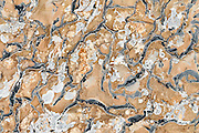 Blue and white patterns penetrate brown sedimentary rocks at Dawson Pass in Glacier National Park, Montana, USA. Since 1932, Canada and USA have shared Waterton-Glacier International Peace Park, which UNESCO declared a World Heritage Site (1995) containing two Biosphere Reserves (1976). Rocks in the park are primarily sedimentary layers deposited in shallow seas over 1.6 billion to 800 million years ago. During the tectonic formation of the Rocky Mountains 170 million years ago, the Lewis Overthrust displaced these old rocks over newer Cretaceous age rocks.