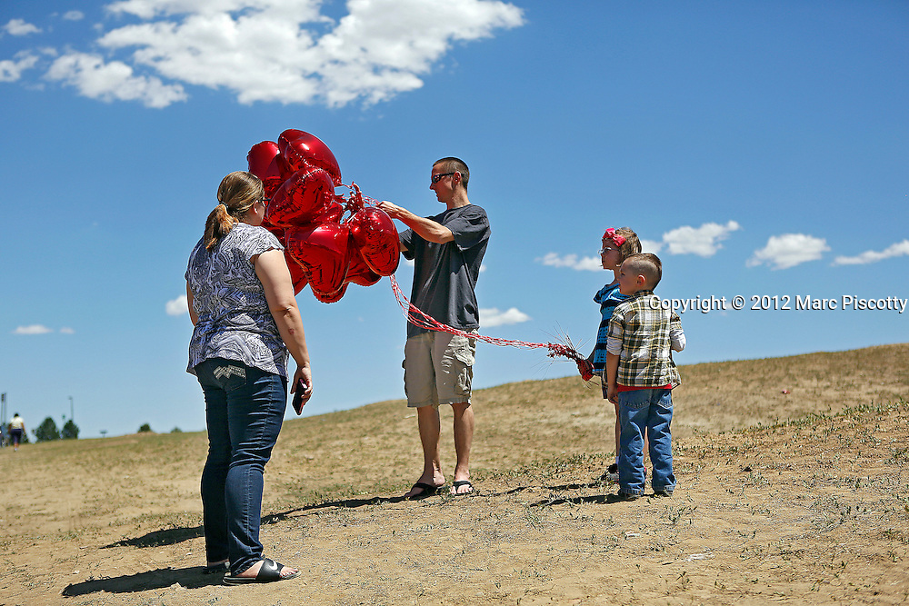 SHOT 7/21/12 2:12:23 PM - Eric and Sophia Gettys of Aurora, Colo. help their children Gabriel, 4, and Gabriela, 6, with 12 red heart shaped balloons that they placed at a makeshift memorial near the Century 16 Movie Theaters at the Aurora Town Center in Aurora, Colo. The family had planned to go to a movie at another theater to get their minds off the tragedy but found it closed because one of the shooting victims had worked there so they saw it as a sign to visit the memorial and leave one balloon for each victim. James Eagan Holmes will face charges in the shootings that occurred on Friday July 20, 2012 in which twelve people were killed and another 58 were injured. (Photo by Marc Piscotty / © 2012)