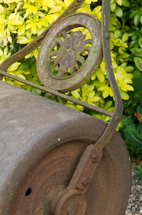 A rusty antique metal garden lawn roller