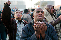 An Egyptian man in Tahrir Square holds his hands up in prayer while watching rocks and the occasional molotov cocktail fly in a battle between anti-government demonstrators (of which he is one) and pro-Mubarak forces less than 100 meters away. (Cairo, Egypt - February 2, 2011)