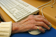 An elderly woman using a computer mouse.