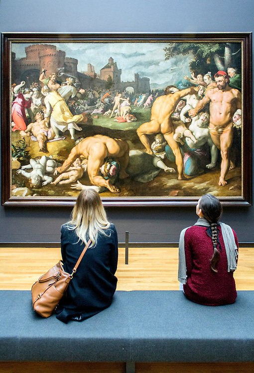 AMSTERDAM, NETHERLANDS - FEBRUARY 08: Visitor at Rijksmuseum admiring The Massacre of the Innocents, Cornelis Cornelisz. van Haarlem, on February 08, 2015 in Amsterdam. The Rijksmuseum is located at the Museum Square, and first opened its doors in 1885.